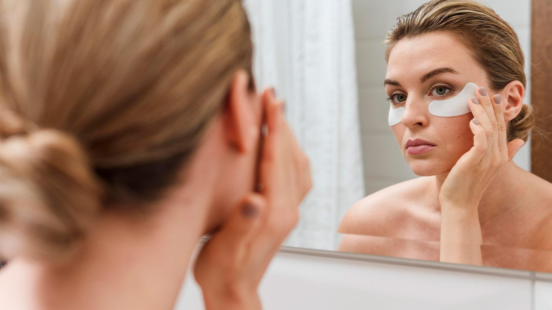 mulher se olhando no espelho com adesivos para olheiras